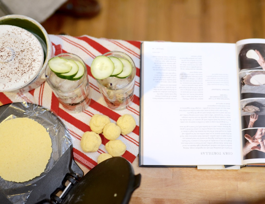 tortilla in a taco press with two glasses garnished with cucumber