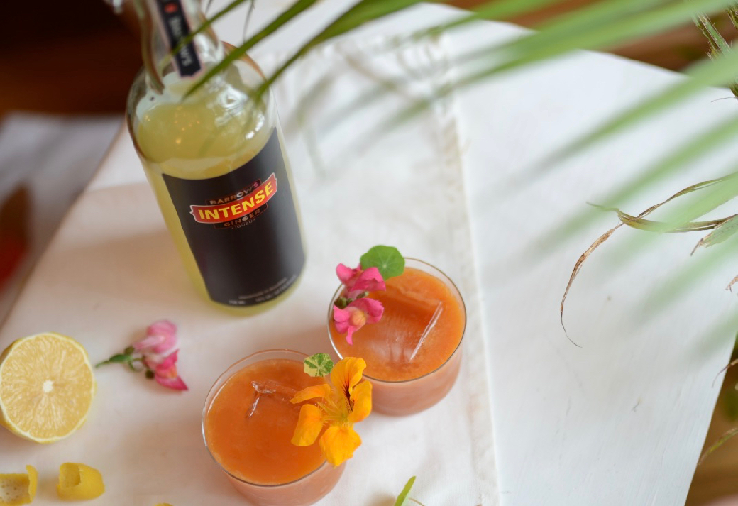 barrows intense ginger liqueur with a palm tree and two cocktails with flowers