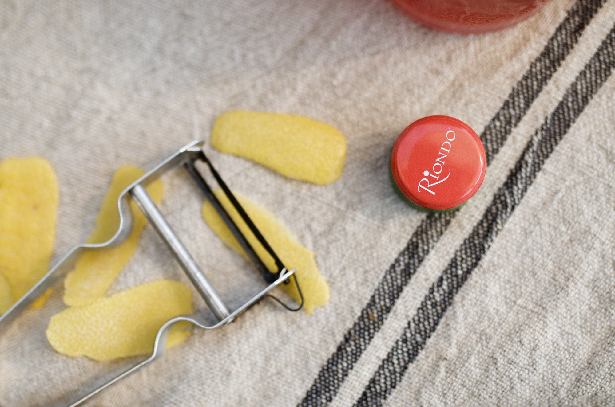 riondo bottle cap and a peeler with lemon garnishes